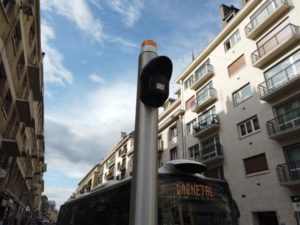 The audio signals are fixed at the top of the pole warning a bus of a visually impaired pedestrian